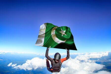 Pakistan extreme. Flag in skydiving. People in free fall grab flag of Pakistan. Patriotism, men and flag.