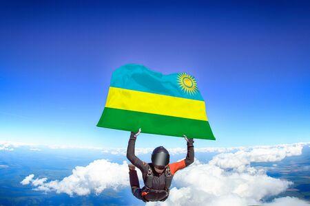 Rwanda extreme. Flag in skydiving. People in free fall grab flag of Rwanda. Patriotism, men and flag.