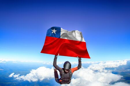 Chile extreme. Flag in skydiving. People in free fall grab flag of Chile. Patriotism, men and flag.