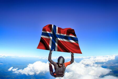 Norway extreme. Flag in skydiving. People in free fall grab flag of Norway. Patriotism, men and flag. Фото со стока