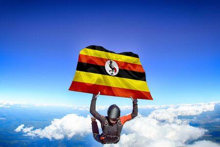 Uganda extreme. Flag in skydiving. People in free fall grab flag of Uganda. Patriotism, men and flag. Фото со стока