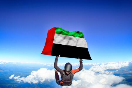 Kuwait extreme. Flag in skydiving. People in free fall grab flag of Kuwait. Patriotism, men and flag. Фото со стока