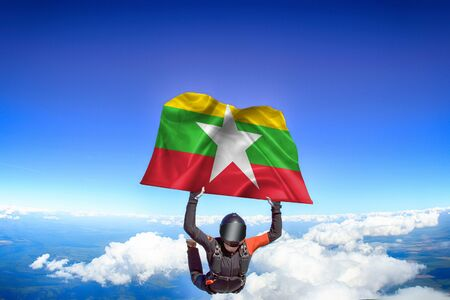 Myanmar extreme. Flag in skydiving. People in free fall grab flag of Myanmar. Patriotism, men and flag. Фото со стока