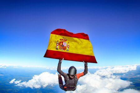 Spain extreme. Flag in skydiving. People in free fall grab flag of Spain. Patriotism, men and flag.