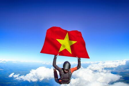 Vietnam extreme. Flag in skydiving. People in free fall grab flag of Vietnam. Patriotism, men and flag.