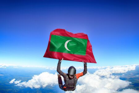 Maldives extreme. Flag in skydiving. People in free fall grab flag of Maldives. Patriotism, men and flag. Фото со стока