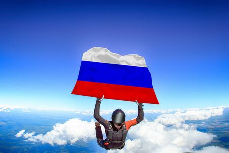 Russia extreme. Flag in skydiving. People in free fall grab flag of Russia. Patriotism, men and flag.
