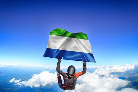 Sierra Leone extreme. Flag in skydiving. People in free fall grab flag of Sierra Leone. Patriotism, men and flag. Фото со стока