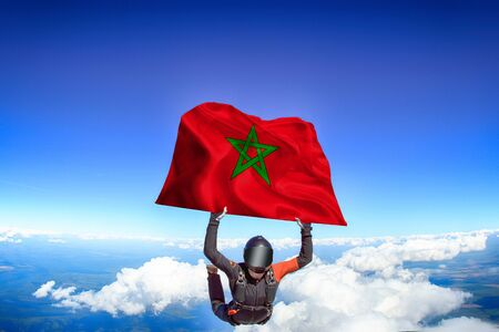 Morocco extreme. Flag in skydiving. People in free fall grab flag of Morocco. Patriotism, men and flag.