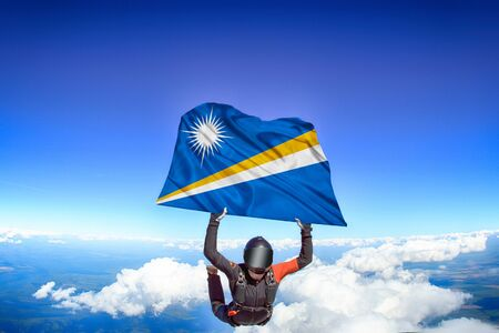 Marshall Islands extreme. Flag in skydiving. People in free fall grab flag of Marshall Islands. Patriotism, men and flag. Фото со стока