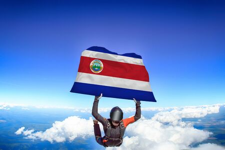 Costa Rica extreme. Flag in skydiving. People in free fall grab flag of Costa Rica. Patriotism, men and flag.