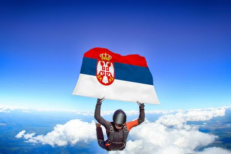 Serbia extreme. Flag in skydiving. People in free fall grab flag of Serbia. Patriotism, men and flag.