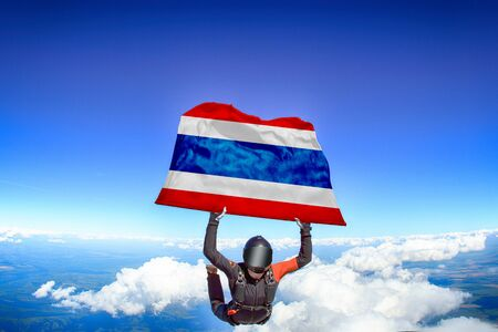 Thailand extreme. Flag in skydiving. People in free fall grab flag of Thailand. Patriotism, men and flag.