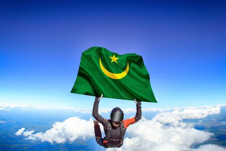 Mauritania extreme. Flag in skydiving. People in free fall grab flag of Mauritania. Patriotism, men and flag.