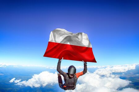 Poland extreme. Flag in skydiving. People in free fall grab flag of Poland. Patriotism, men and flag.