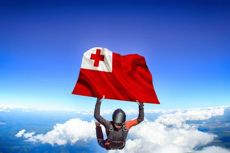 Tongo extreme. Flag in skydiving. People in free fall grab flag of Tongo. Patriotism, men and flag. Фото со стока
