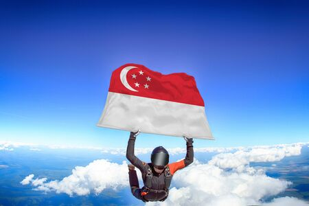 Singapore extreme. Flag in skydiving. People in free fall grab flag of Singapore. Patriotism, men and flag. Фото со стока