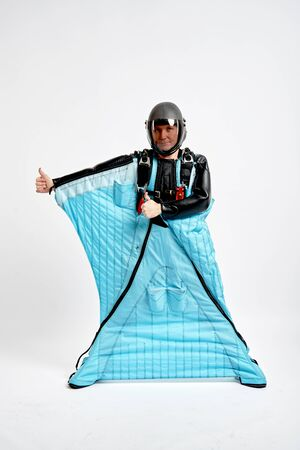 Class. Men in wing suit shows gesture of approval. Skydiving men in parashute. Simulator of free fall.