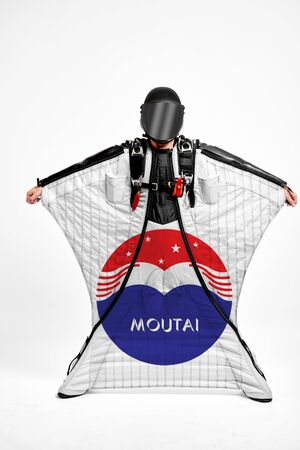 Kweichow Moutai. Men in wing suit demonstrations popular brands. Men simulates of free fall.  Banco de Imagens