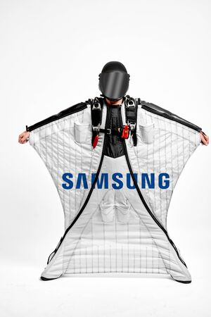 Samsung. Men in wing suit demonstrations popular brands. Men simulates of free fall.