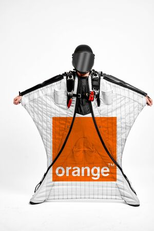 Orange. Men in wing suit equipment.Demonstration of popular brands. Simulator of free fall.