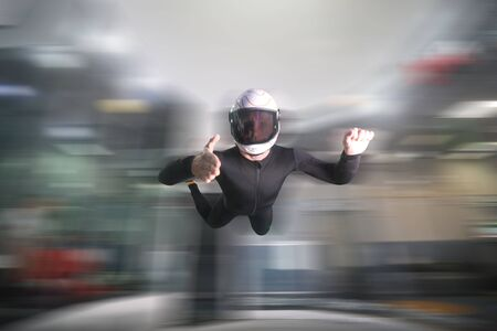 Greeting gesture. Fly men shows greeting gesture with hands. Sky diver gestures by fingers. Teampleat skydiver.