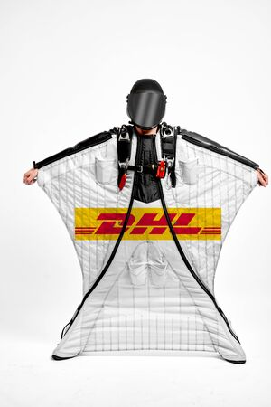 DHL. Men in wing suit demonstrations popular brands. Men simulates of free fall.  Banco de Imagens