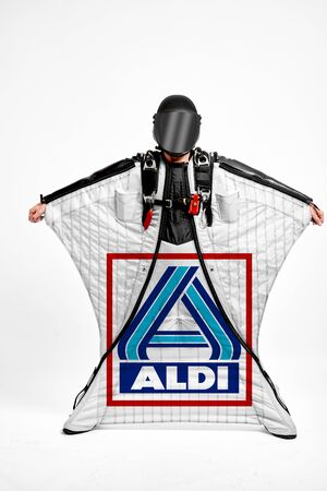 Aldi. Men in wing suit demonstrations popular brands. Men simulates of free fall.  Banco de Imagens