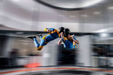 Up. Extreme people prefere sky sport. Fly men perfoms trick in air. Parachutist in blue and yellow suit is in free fall. Skydiving is sport without rules. Imagens