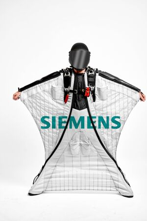 Siemens. Men in wing suit demonstrations popular brands. Men simulates of free fall.  Banco de Imagens