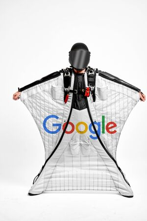 Google Inc. Men in wing suit demonstrations popular brands. Men simulates of free fall.  Banco de Imagens