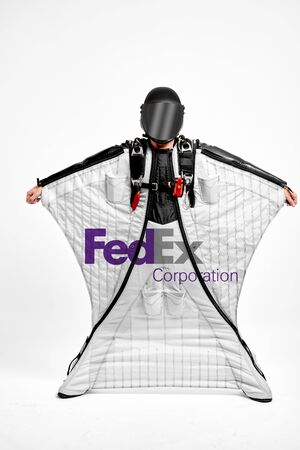 FedEx. Men in wing suit demonstrations popular brands. Men simulates of free fall. Stock Photo