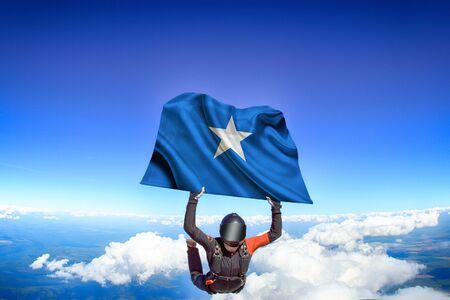 Somalia extreme. Flag in skydiving. People in free fall grab flag of Somalia. Patriotism, men and flag.