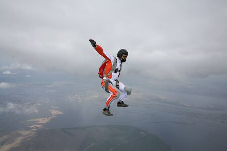 Skydiving. Fly men is a pilot of his body in air. Extreme people prefer skydiving. Parachutist in orange suit. Free lifestyle.