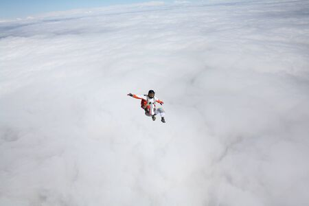 Activity. Men with parachute equipment have wings. Skydiver is flying in open air. Parachutist in blue suit is in free fall. No gravitation in sky. Reklamní fotografie