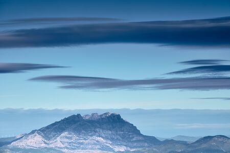 Granite mountain with blue atmosphere and big clouds, Montserrat, Catalonia