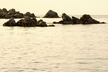 Rocks illuminated laterally by natural light in calm sea