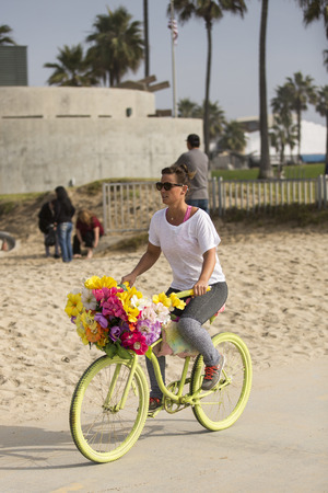 VENICE BEACH, UNITED STATES - January 3  Girl riding a bicycle by the beach promenade on January 3, 2014 in Venice Beach