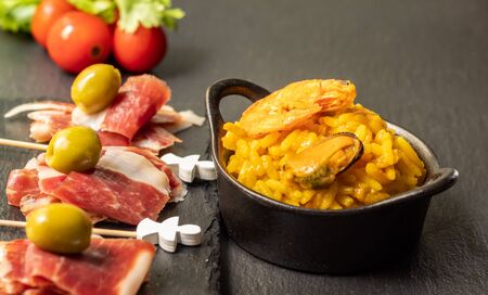 Spanish tapas, Iberian ham, Valencian paella and olives 写真素材