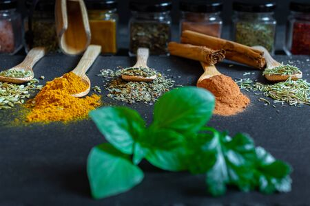 Spices and herbs of various colors in wooden spoons on black slate stone