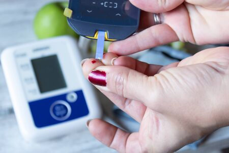 Woman checking her blood glucose with glucometer