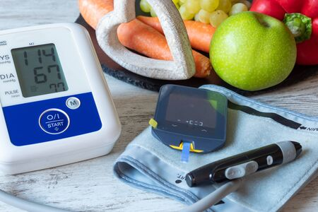 Devices for measuring blood pressure and blood glucose on a table with fruit and vegetables