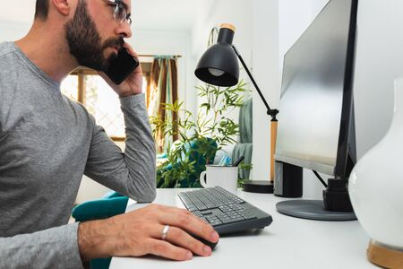 Man working from home with computer and mobile phone