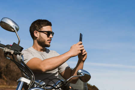 Biker sitting on the motorcycle taking a picture of the landscape with the mobile Stock fotó