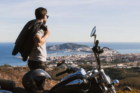 Biker with sunglasses and leather jacket on his shoulder looking at the horizon