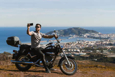Biker sitting on the motorcycle taking selfie with the landscape with the mobile