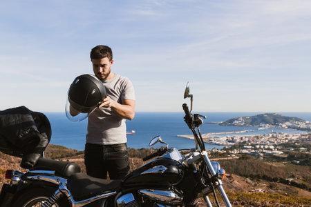 Biker putting on helmet in the field