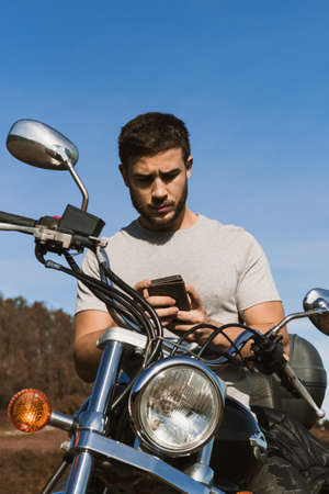 Biker looking at the mobile during a route