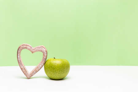 Apple and heart on horizontal green and white background