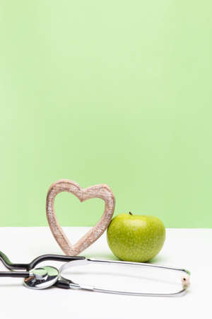 Apple, heart and stethoscope on vertical green and white background